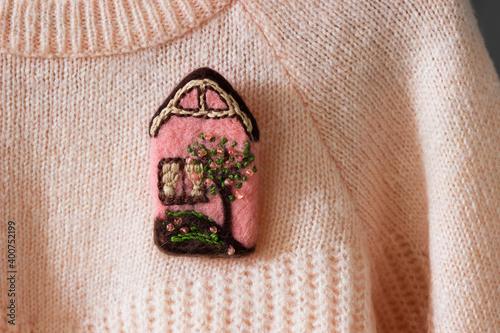 Wallpaper Mural Handmade wool brooch on a sweater background. Selective focus.