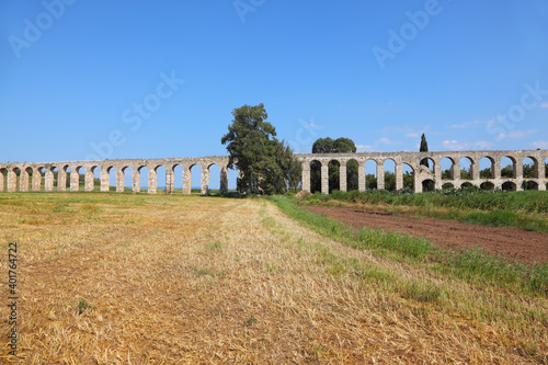 Foto A Roman aqueduct on grassy meadow