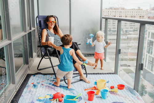Foto Young mother spending time together with children babies on balcony at home