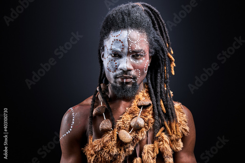 Photo african shirtless guy with colourful make-up isolated on dark studio background,