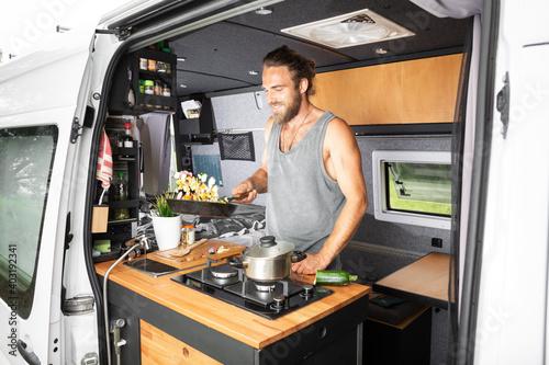 Smiling man cooking inside his camper van Fototapeta