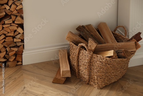 Valokuva Basket with firewood on floor in room