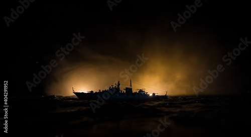 Fotografía Silhouettes of a crowd standing at blurred military war ship on foggy background