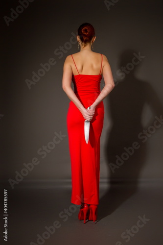 Wallpaper Mural Elegant girl in a red evening dress holds in her hand a large sharp steel kitche