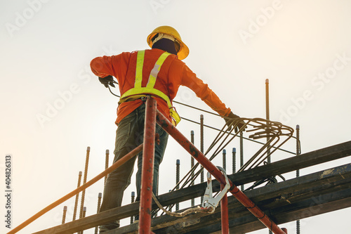 Vászonkép Workers are working on construction site, labors wearing vest and safety helmet, construction crews on steel work at the building