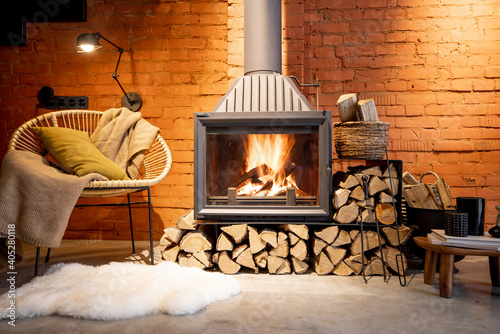 Valokuva Cozy fireplace with firewood in the loft style home interior with brick wall bac
