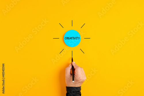 The word creativity written on a blue circle badge with male hand drawing rays around it.