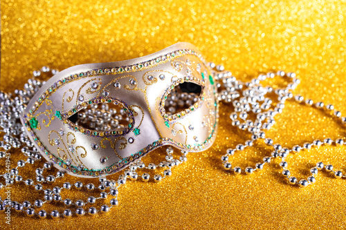 Canvas Print Festive, colorful Mardi Gras or carnivale mask and beads on golden background