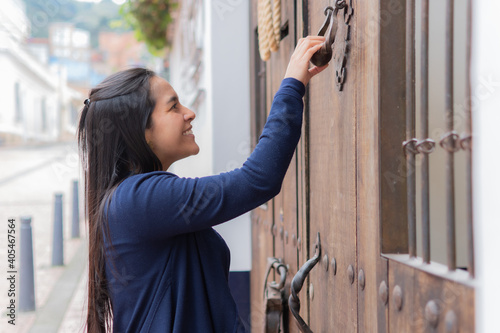 Foto Young happy Hispanic female in a blue jacket knocking on the door