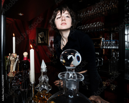 A young girl, dressed in a gothic style, poses in a posh alcoholic bar in red and black colors Fototapeta