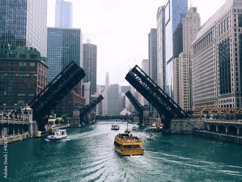 Fototapeta Ferries Sailing On River By Modern Buildings In City Against Clear Sky