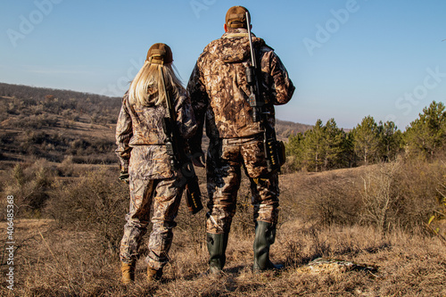 Valokuva A man and a woman in hunting suits and with rifles stand on the hill, the hunter