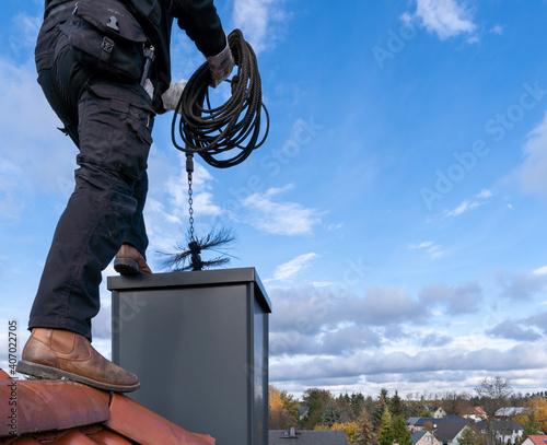 Chimney sweep man in work uniform cleaning chimney on building roof Fototapet