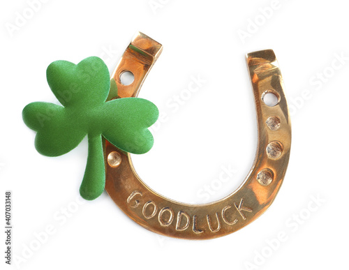 Fototapeta Golden horseshoe and decorative clover leaf on white background, top view