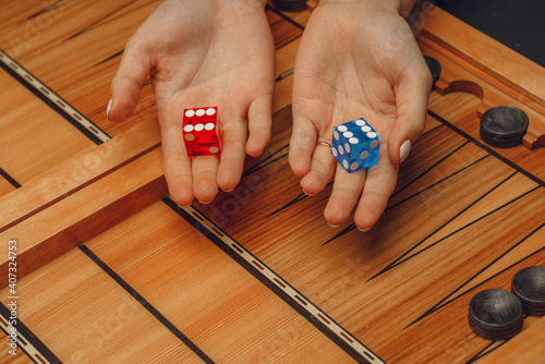 Fotografia, Obraz wooden backgammon and girl's hands with bones for the game