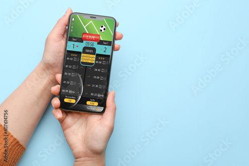 Wallpaper Mural Female hands with open page of online betting site on screen of mobile phone aga