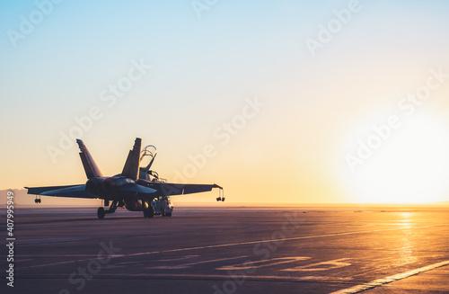 Fotografiet Jet fighter on an aircraft carrier deck against beautiful sunset sky