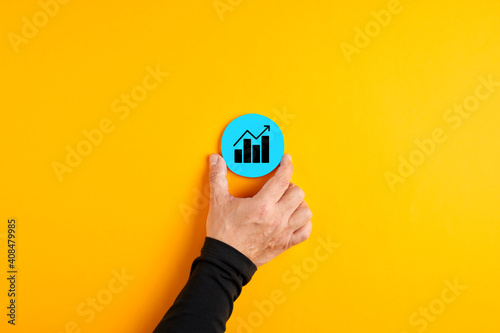 Fotografia Male hand placing a blue badge with a business chart or graph with an increasing