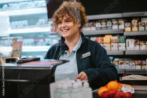 Happy cashier at supermarket checkout Fototapete