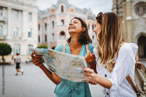 Fun, friends, travel and tourism concept. Beautiful girls looking for direction in the city