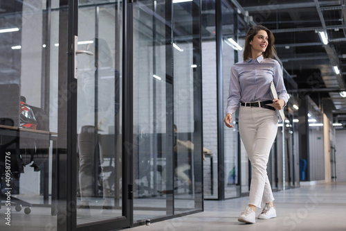 Canvas Print Businesswoman walking along the office corridor with documents.