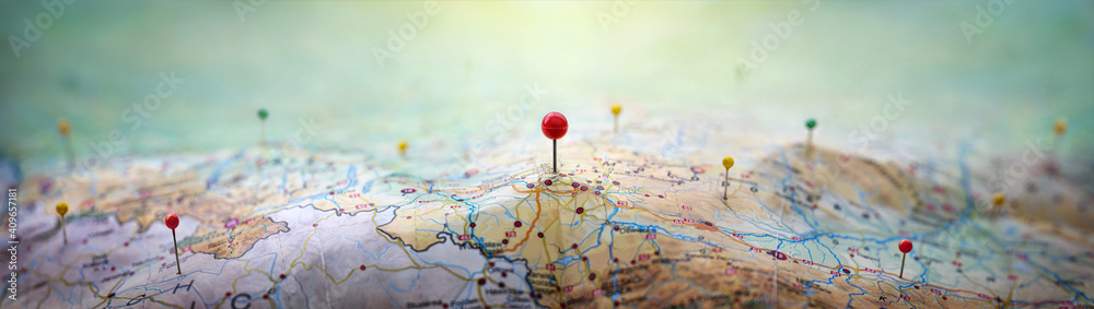 Pins on a geographic map curved like mountains. Pinning a location on a map with mountains. Adventure,  geography, mountaineering, hike and travel concept background.