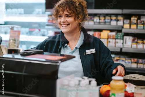 Canvas Print Cashier working at supermarket checkout