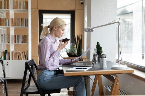 Female millennial entrepreneur giving command to virtual assistant on cellphone, Fototapeta