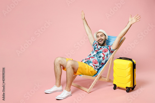 Fotografía Full length of cheerful young traveler tourist man in summer clothes hat sit on deck chair rising spreading hands isolated on pink background