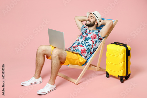 Wallpaper Mural Full length smiling traveler tourist man in hat sit on deck chair work on laptop computer hold hands behind head isolated on pink background