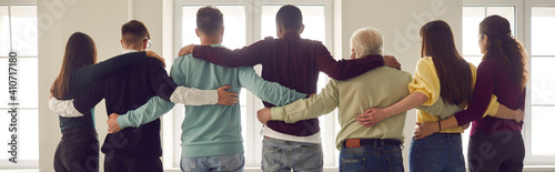 Obraz na plátne Team of people hug standing in a row with their backs to the camera and looking out the window