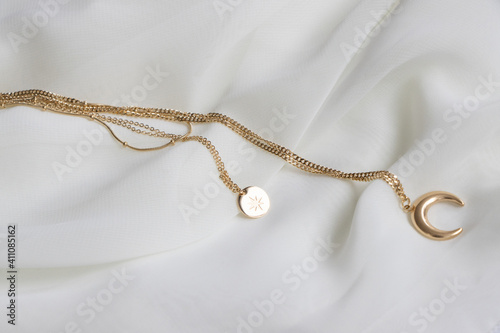 Fotografie, Obraz Closeup of a golden necklace with a moon and sun shaped pendant