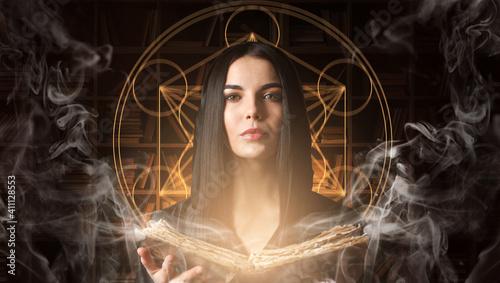Fotografie, Obraz Female alchemist with book on dark background