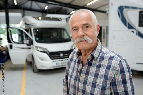 portrait of senior man in campervan garage Fotobehang