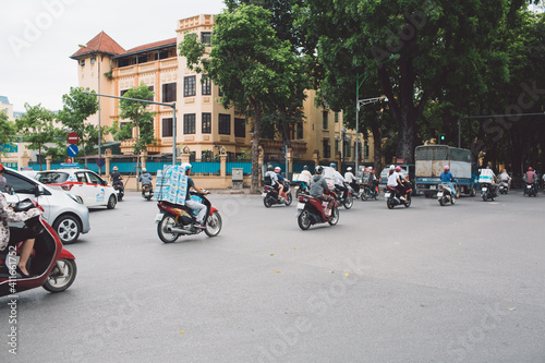 People Riding Motorcycles On Road By Buildings In City Against Clear Sky