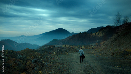 Photo Man Walking On Footpath Against Mountains