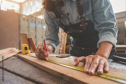 Canvas Print Midsection Of Carpenter Measuring Wood At Workshop
