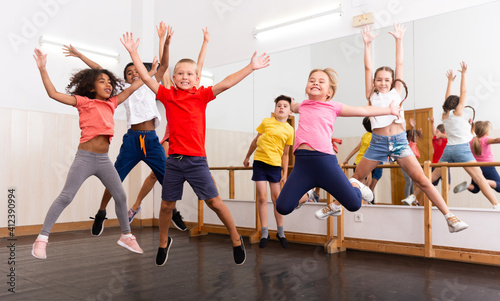Obraz na płótnie Happy kids of different nationalities and ages jumping during class in dance sch