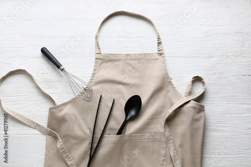 Fotografia Clean apron and kitchen utensils on light wooden background
