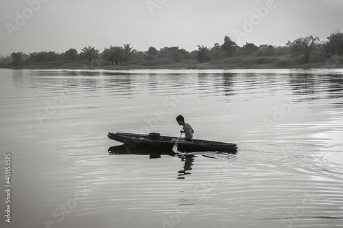 Fotografie, Obraz Side View Of Shirtless Man Rowing Rowboat In Lake
