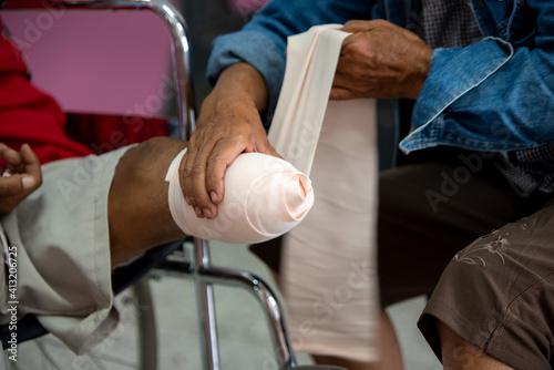 Man Bandaging Handicapped Patient Fotobehang