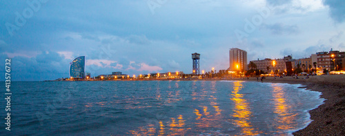 Barcelona Beach panorama in summer night along seaside in Barcelona, Catalonia, Spain. Barceloneta landscape after sunset in blue hour. Mediterranean Sea. Europe tourism and modern city life concept.