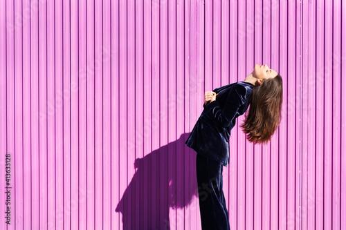 Fototapeta Woman wearing blue suit posing near pink shutter.