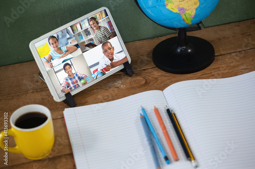 School children learning displayed on tablet screen placed on desk with notebook during video call