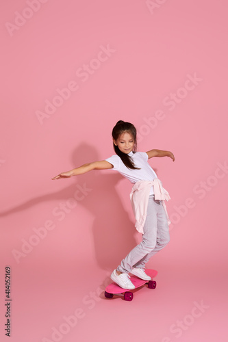 cute happy little child girl riding skateboard against pink background.