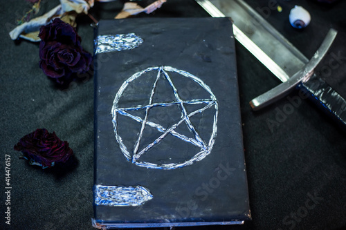 Fototapeta A black book with a pentagram on the cover lies on the table