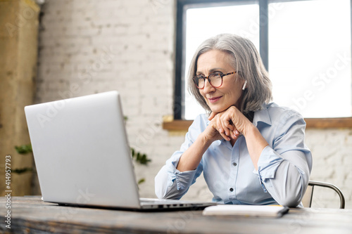 Canvas Print Intelligent elderly gray-haired businesswoman using a laptop in the office
