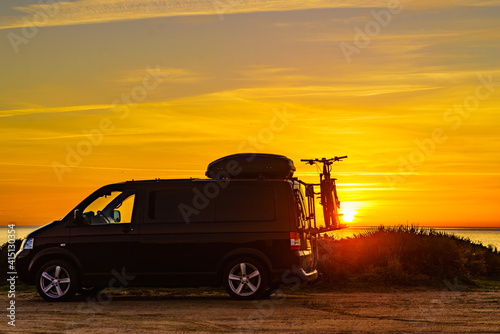 Canvas Camper with bicycles on rack camping on beach at sunrise
