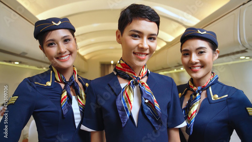 Fotografering Group of cabin crew or air hostess in airplane