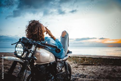 Beautiful girl having fun driving her custom cafe racer motorcycle, enjoying the Fototapeta